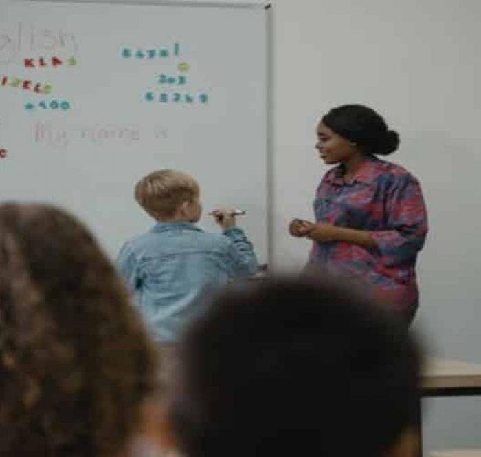 Kid studing English grammar on a blackboard
